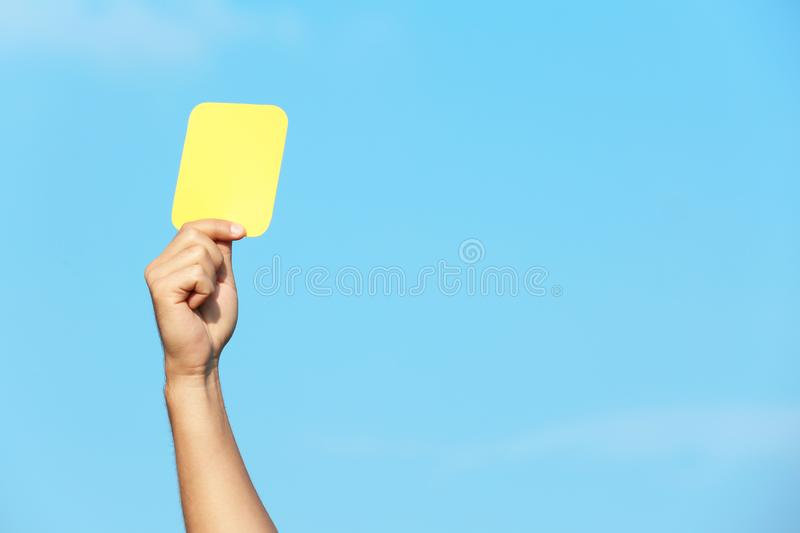 Football referee showing yellow card against blue sky royalty free stock photography