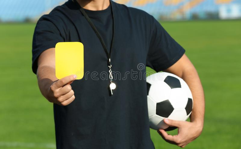 Football referee showing yellow card at stadium stock photography