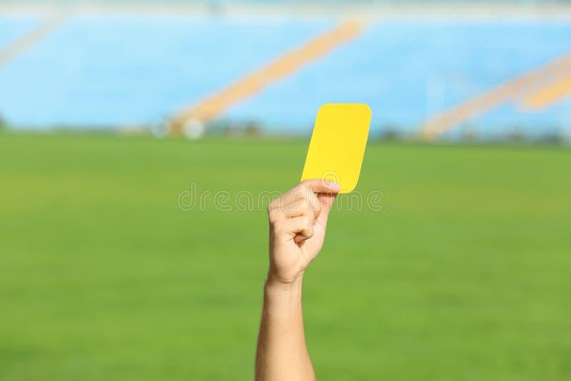 Football referee showing yellow card at stadium royalty free stock image
