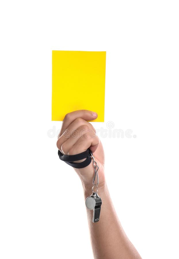 Football referee with whistle holding yellow card on white background royalty free stock image