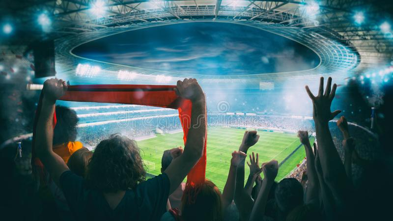 Football scene at night match with with cheering fans at the stadium stock images