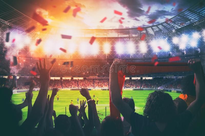 Football scene at night match with cheering fans at the stadium stock photography