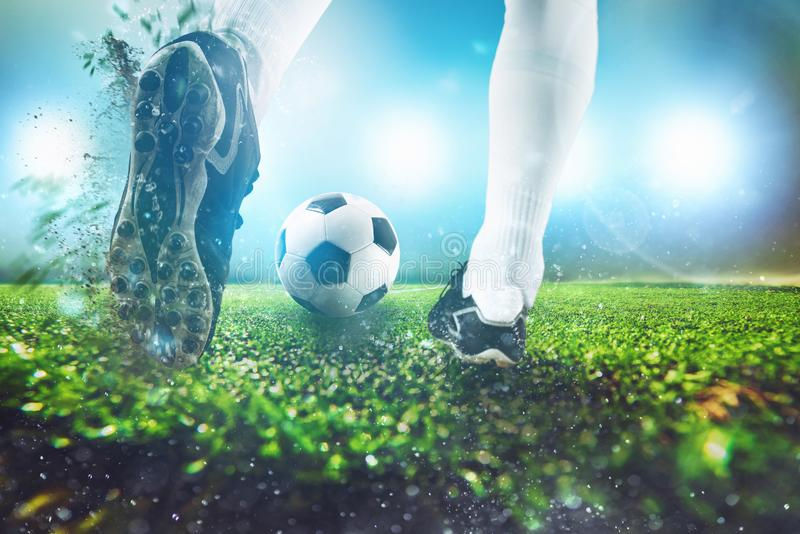 Football scene at night match with close up of a soccer shoe hitting the ball stock photos