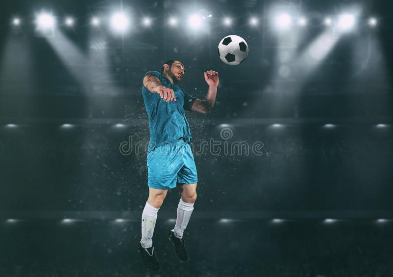 Football scene at night match with player jumping to hit the ball with head royalty free stock photography