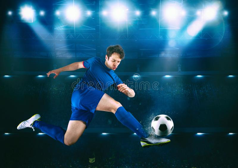 Soccer striker hits the ball with an acrobatic kick in the air at the stadium royalty free stock image