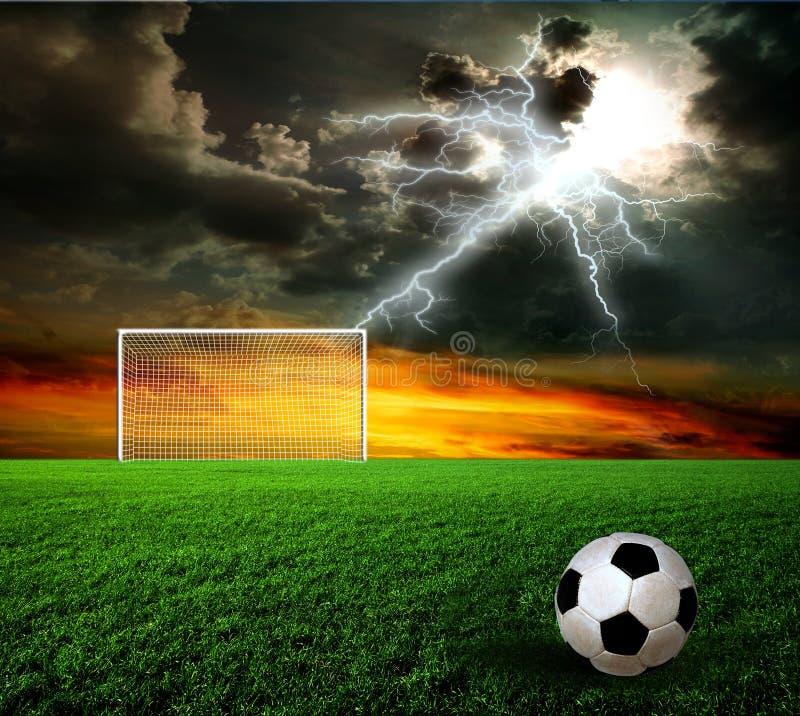 Football, soccer ball. On green grass at sunset stock image