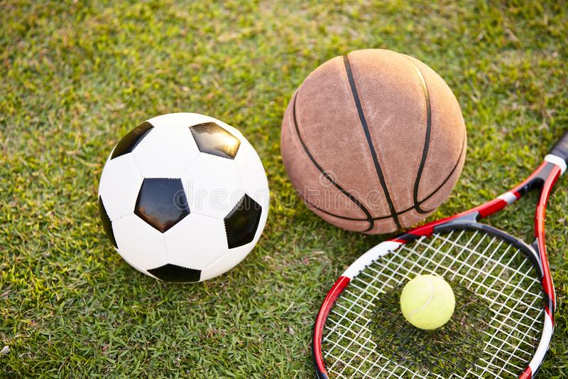 Football basketball and tennis ball and racket on grass royalty free stock photo