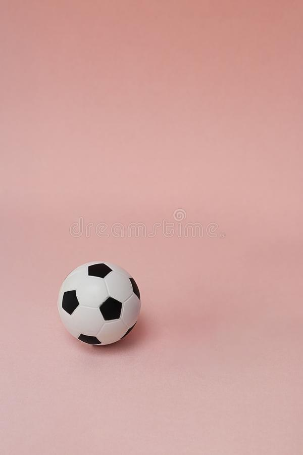 Football or Soccer ball, classic black and white isolated on light pastel coral background. Vertical with copy space. Small soft stock image