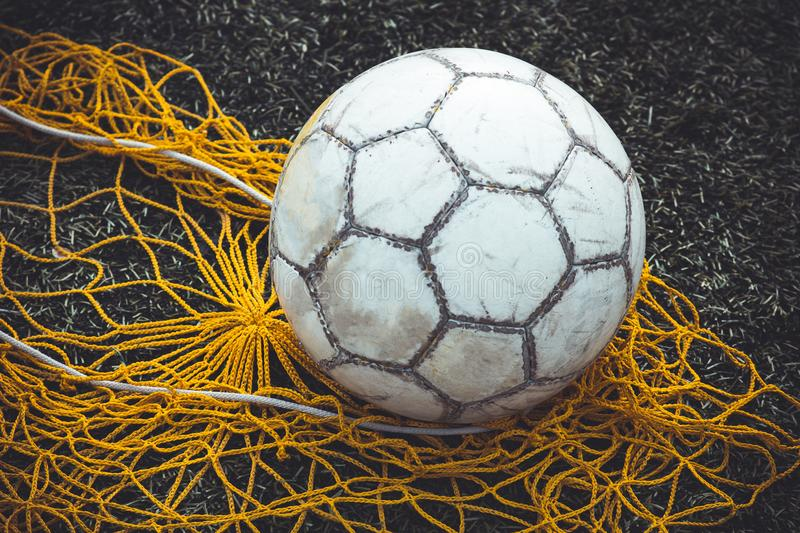 Football or soccer ball on the grass next to the net for balls, close-up stock photography