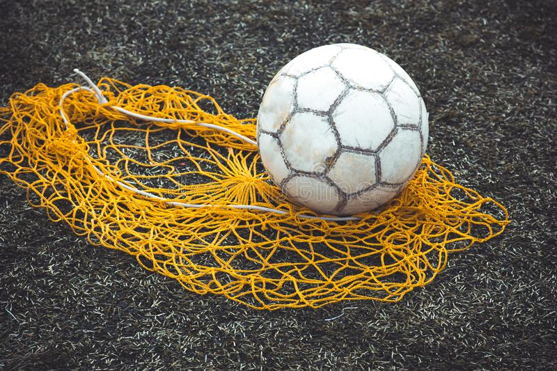 Football or soccer ball on the grass next to the net for balls stock images