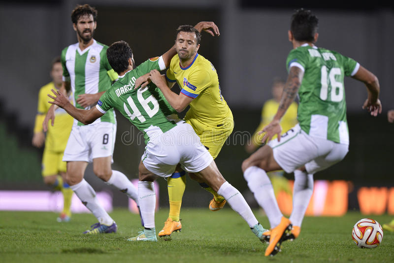 Football or soccer foul. Football players Lucian Sanmartean (yellow kit) and Marcelo dos Santos Ferreira (in white-green kit) fighting for the ball during the stock photos