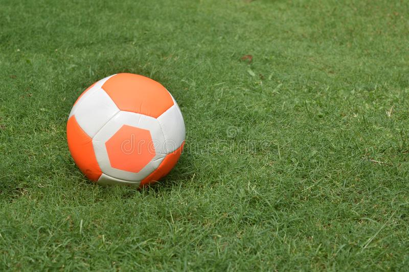 Orange football soccer green grass background copy-space royalty free stock images