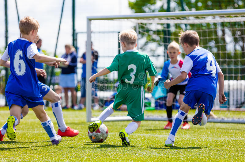 Football soccer match for children. Boys playing football game outdoor. Football soccer match for children. Boys playing football game on a school tournament stock image