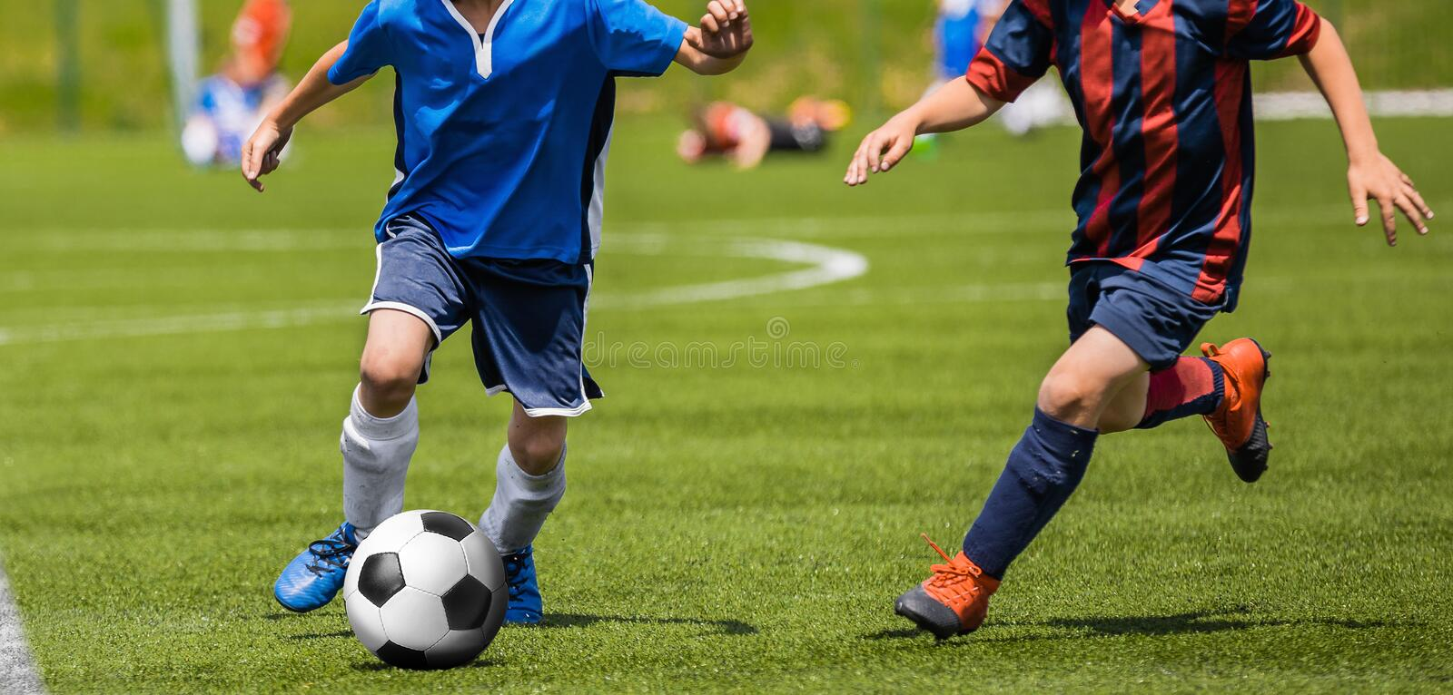 Football Soccer Match for Children. Kids Playing Soccer Game Tournament. Boys Running and Kicking Football. Youth Soccer Coach in the Background stock photo