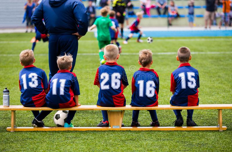 Football soccer match for children. Kids waiting on a bench. Soccer school tournament match. Football school tournament for kids royalty free stock photos