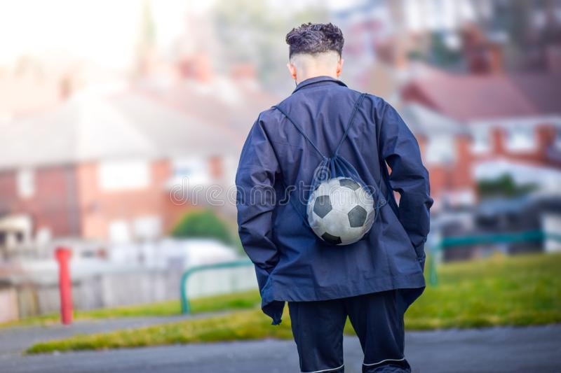 Football soccer player going to training ground in afternoon alone. Back view of football soccer player going to training ground in afternoon alone royalty free stock photo