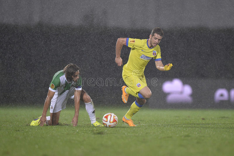 Football or soccer players in action during torrential rain. Football players Alexandru Chipciu (yellow kit) and Tiago Pinto (in white-green kit) fighting for royalty free stock photos