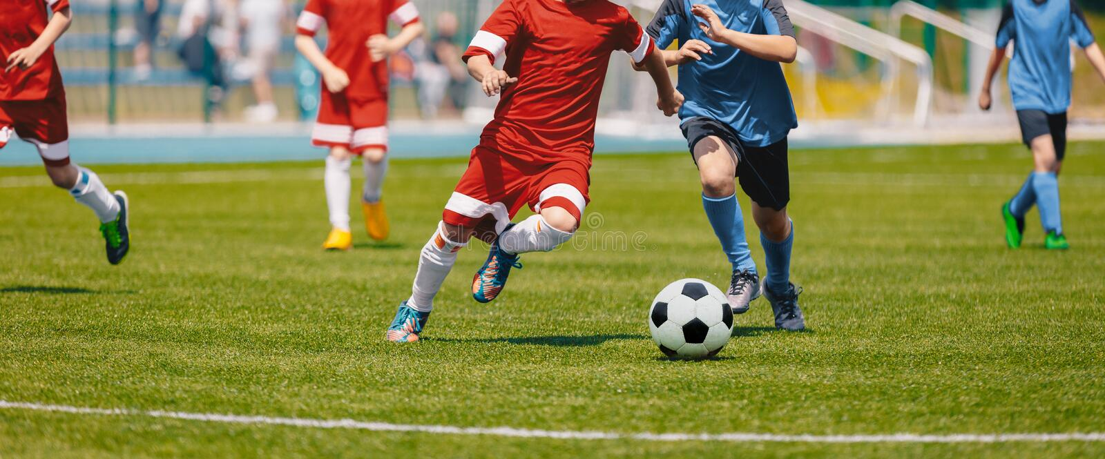 Football Soccer Players Running with Ball. Footballers Kicking Football Match. Young Soccer Players Running After the Ball. Kids in Soccer Red and Blue royalty free stock images