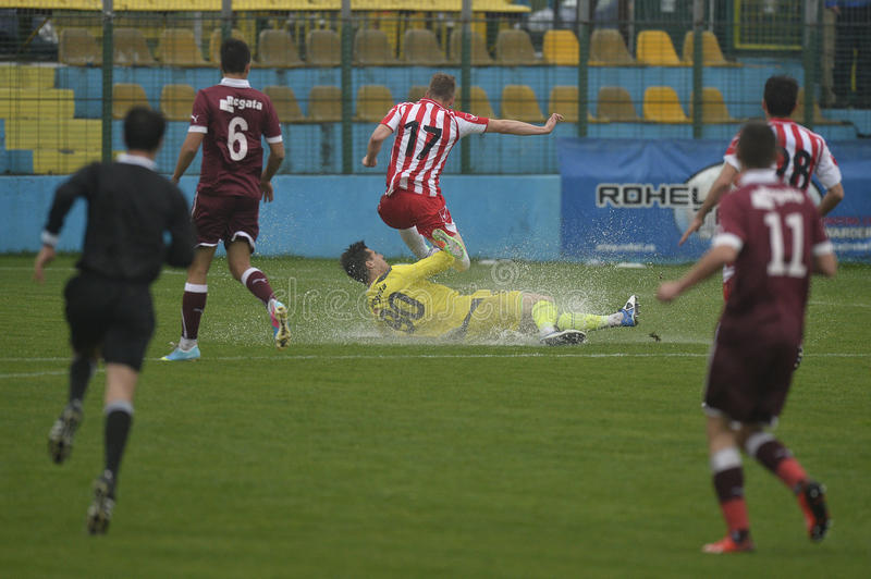 Football or soccer tackle on flooded field stock image