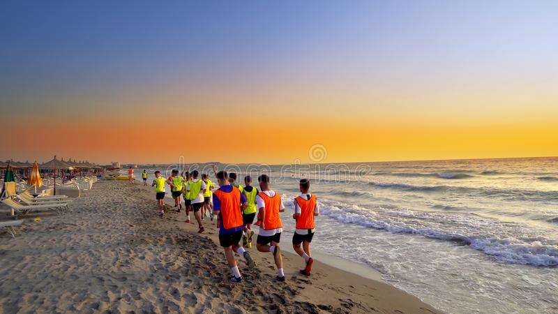 Football team on a beach jogging royalty free stock image