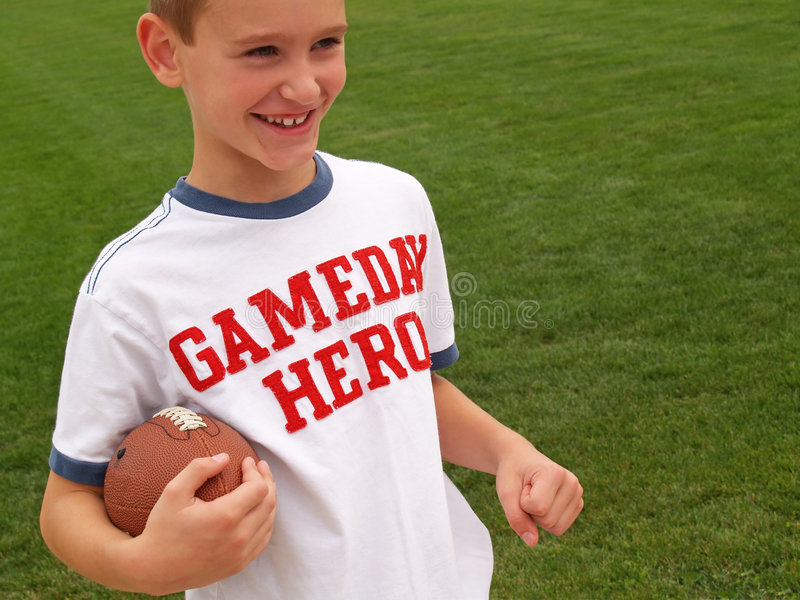 Football star. Young boy playing football and wearing a gameday hero shirt stock photo