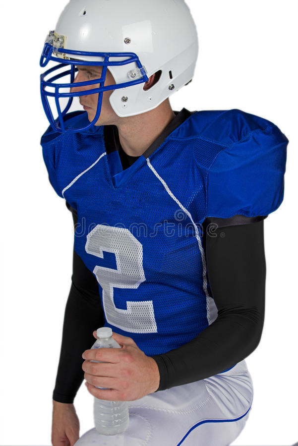Football star taking a knee. Isolated on a white background, an American football player in his helmet and uniform takes a knee while holding onto his refreshing royalty free stock image