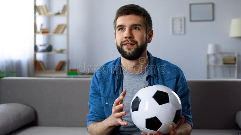 Football supporter attentively watching game on TV, hope of victory championship. Stock photo royalty free stock photo