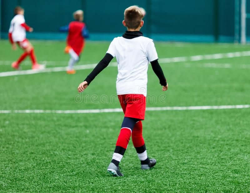 Football teams - boys in red, blue, white uniform play soccer on the green field. boys dribbling. dribbling skills. stock photos