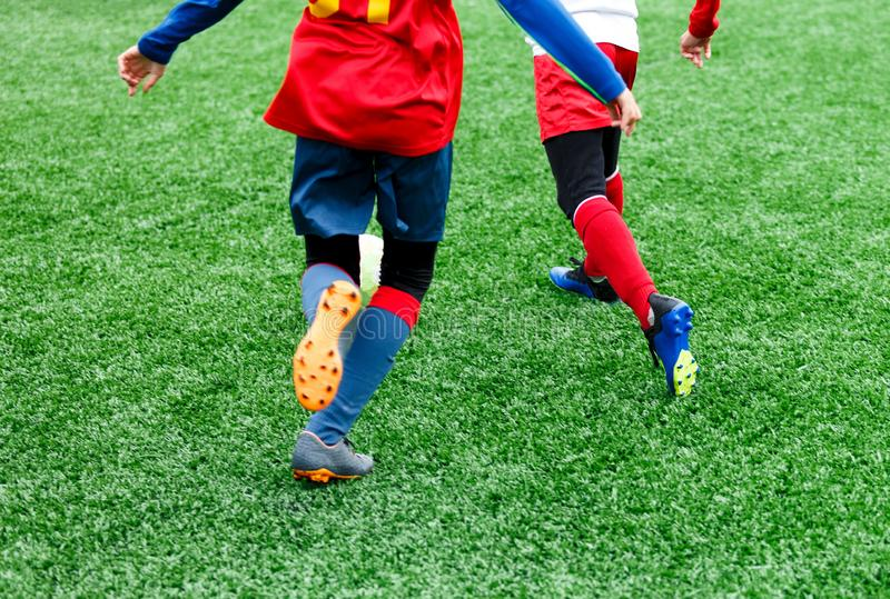 Football teams - boys in red, blue, white uniform play soccer on the green field. boys dribbling. Team game, training, active life. Style, hobby, sport for kids royalty free stock image