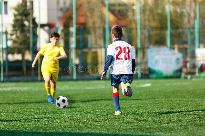 Football teams boys in yellow white sportswear play soccer on the green field. Dribbling skills. Team game, Training stock photography