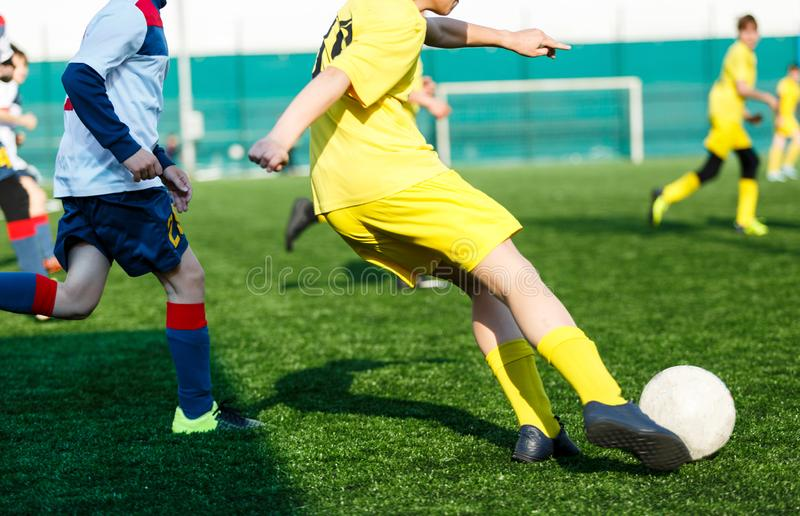 Football teams boys in yellow white sportswear play soccer on the green field. Dribbling skills. Team game, Training. Active lifestyle, hobby, sport for kids royalty free stock photo