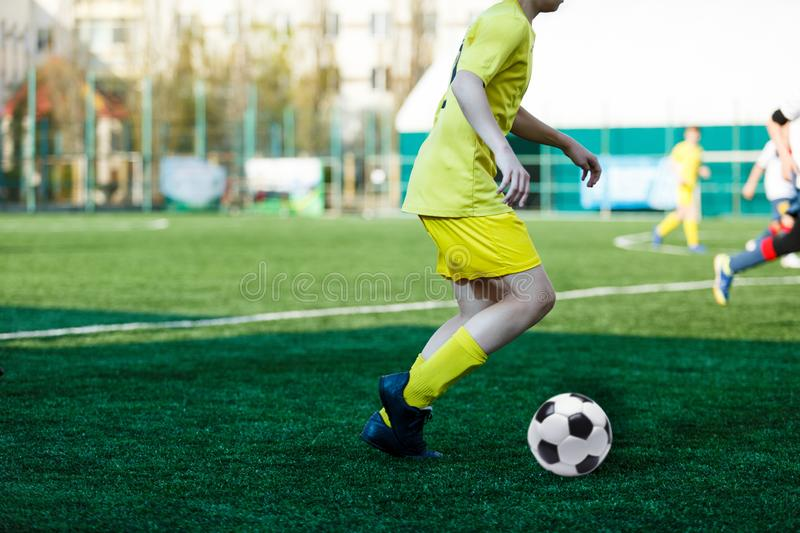 Football teams boys in yellow white sportswear play soccer on the green field. Dribbling skills. Team game, Training,. Active lifestyle, hobby, sport for kids royalty free stock photos