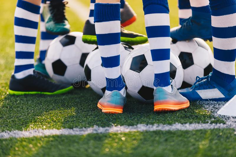 Football Training. Legs of Young Soccer Boys. Football Academy Team Training with Balls. Children Practicing Soccer. Soccer Balls Under Players Foot On Green royalty free stock image