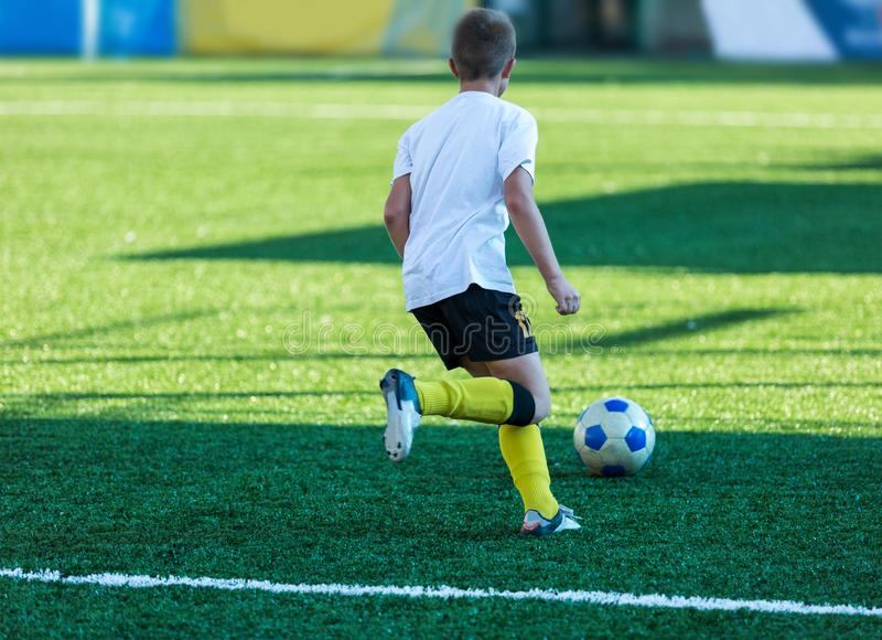 Football training soccer for kids. Boy runs kicks dribbles soccer balls. Young footballers dribble and kick football ball in game. Training, active lifestyle royalty free stock images
