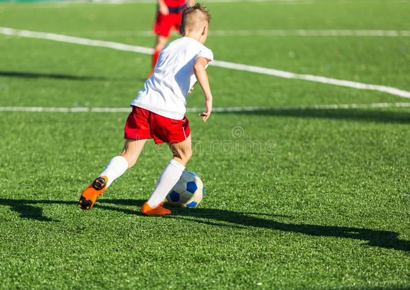Football training soccer for kids. Boy runs kicks dribbles soccer balls. Young footballers dribble and kick football ball in game. Training, active lifestyle royalty free stock image
