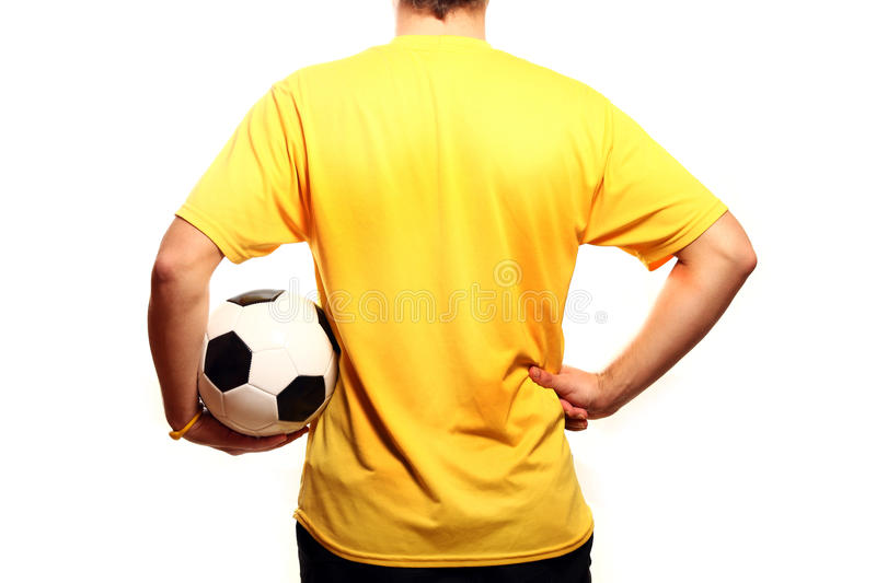 Footballer. A picture of a young footballer in a yellow t-shirt with a football over white background stock photography