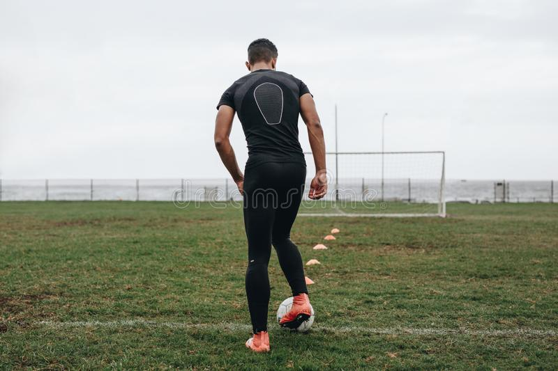Footballer practicing dribbling skills. Rear view of a soccer player practicing dribbling with the help of cones arranged on field. Football player practicing on royalty free stock image