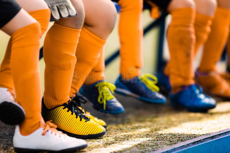 Footballers in soccer cleats. Youth athletes in soccer clothes. Young football players wearing football clothes and soccer shoes sitting on bench in a row royalty free stock photo