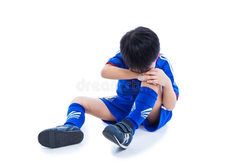 Footballeur asiatique de la jeunesse pleurant pour une blessure au genou douloureuse complètement images stock