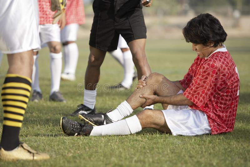 Footballeur blessé s'asseyant sur le lancement image libre de droits