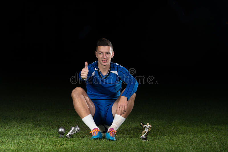 Footballeur célébrant Victory While Holding Win Coup image libre de droits
