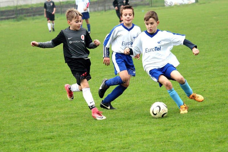 Footballeur d'enfant défendre la boule avant son rival photo libre de droits