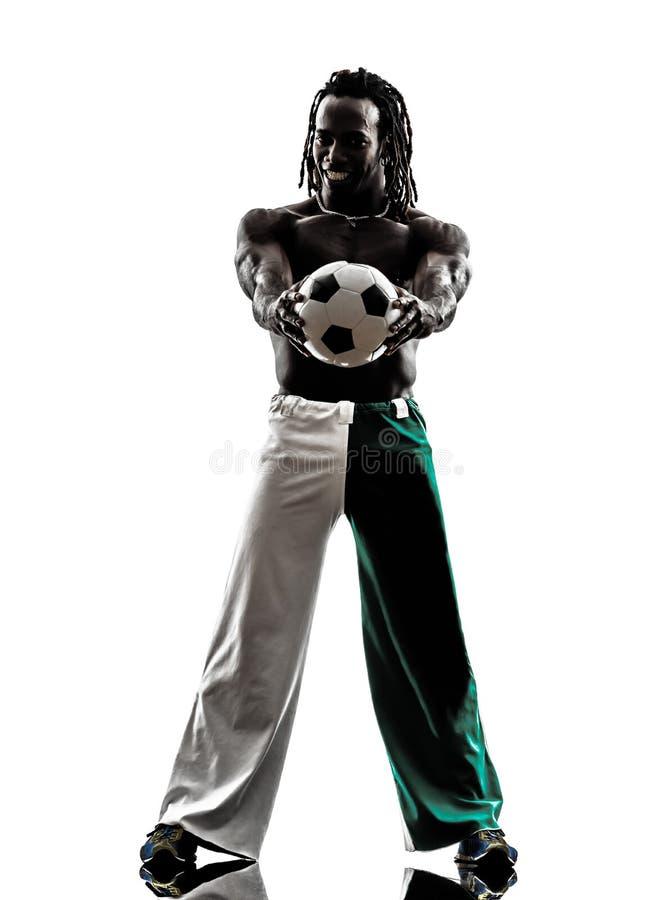 Footballeur d'homme de couleur tenant montrer la silhouette du football photographie stock libre de droits