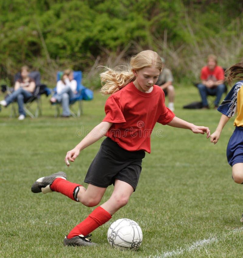 Footballeur de l'adolescence de la jeunesse donnant un coup de pied la bille image libre de droits