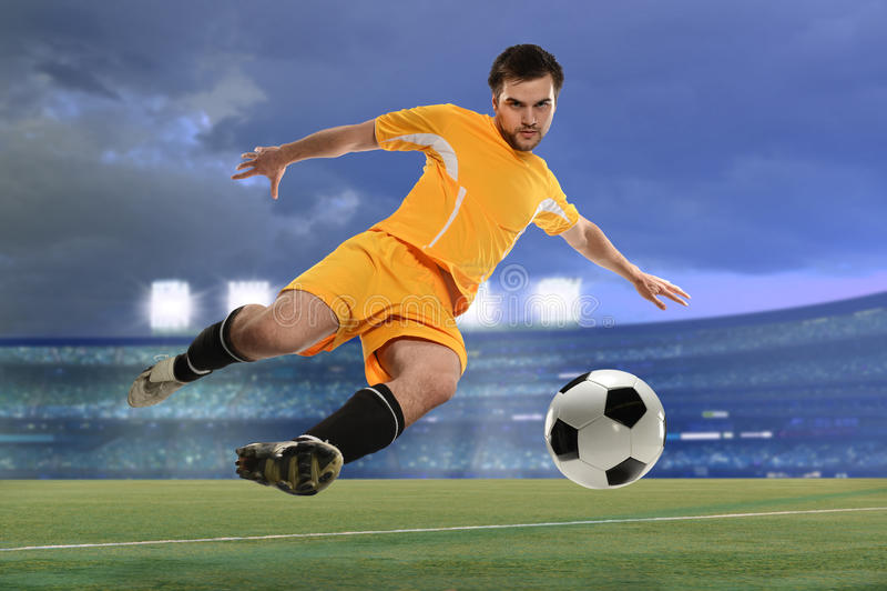 Footballeur donnant un coup de pied la bille photos libres de droits
