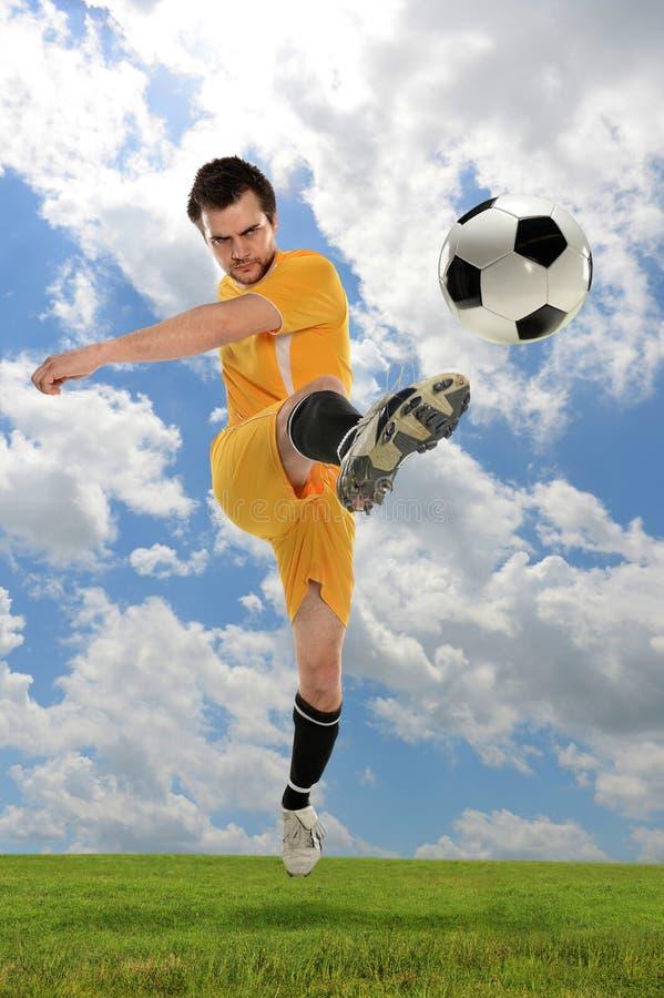 Footballeur donnant un coup de pied la bille photographie stock libre de droits