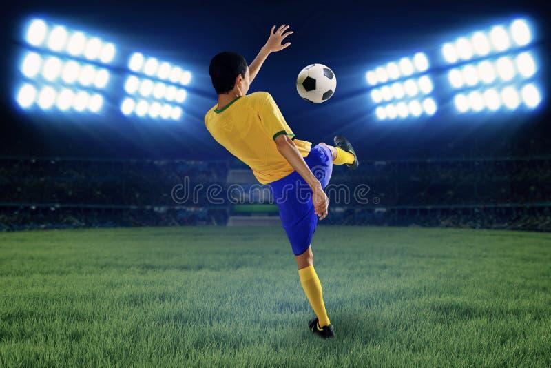 Footballeur donnant un coup de pied la boule le champ photo libre de droits