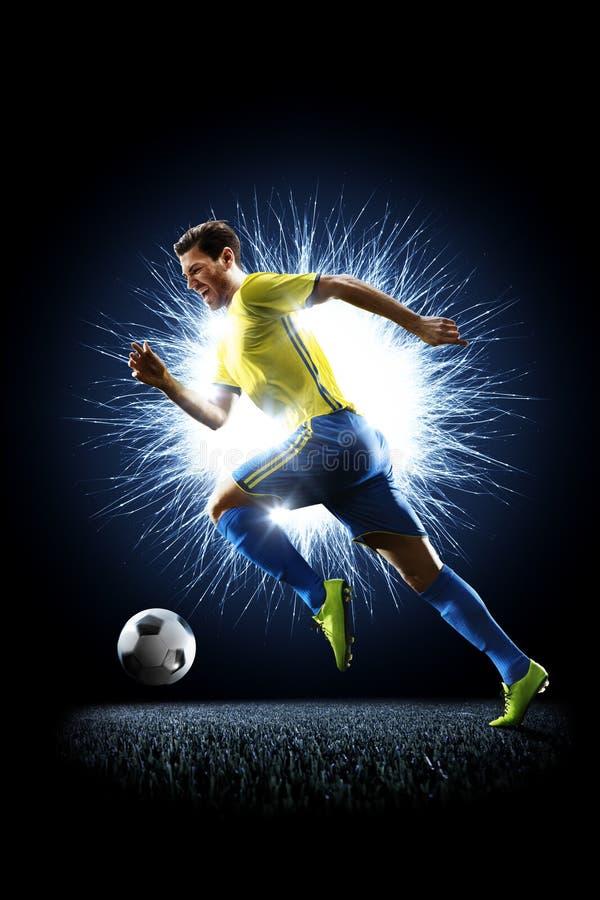 Footballeur du football professionnel dans l'action sur le noir photo libre de droits