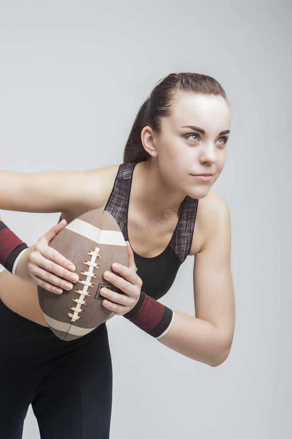 Footballeur féminin de Professioanl avec la boule pour l'Américain Footbal photographie stock