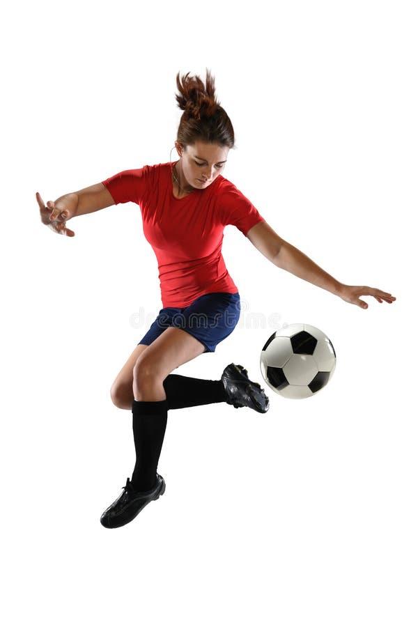 Footballeur féminin donnant un coup de pied la boule image stock
